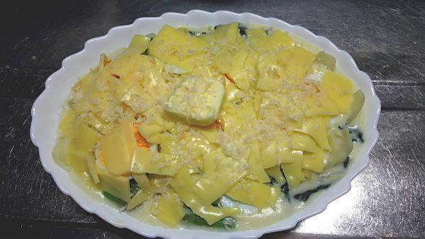 耐熱皿に盛ったマカロニグラタンにチーズとバターとパン粉をトッピング
